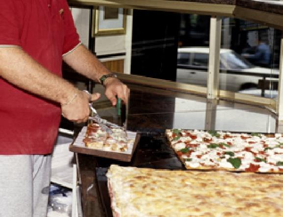切り売り店の特徴、四角く焼いたピザを丁寧に切り分ける。