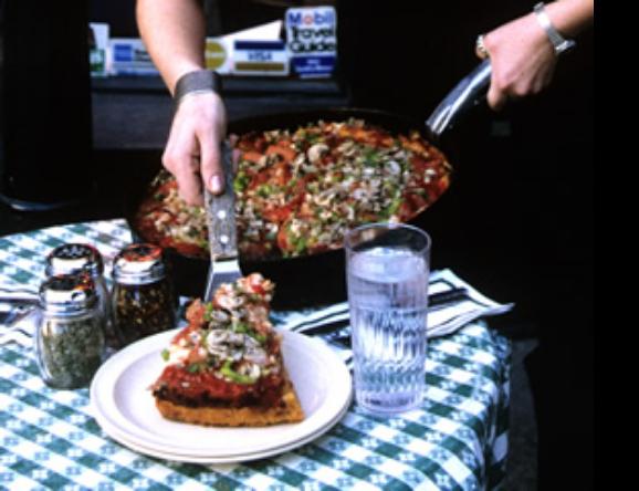 深めの鉄のパンに入れられたままサーブされる具だくさんのディープディッシュ・ピザ